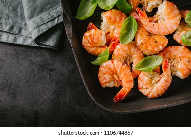 Fried grilled prawns with fresh herbs and basil on grill pan on dark background with green kitchen towel. Top view with place for text
