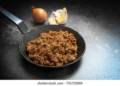 fried ground beef with onion and garlic in a black pan on a dark stone background with copy space, selected focus, narrow depth of field