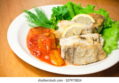 Fried haddock fish with vegetables and greens on white plate