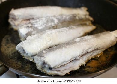 Fried hake fish fillet in a frying pan at kitchen