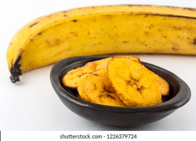 Fried half ripe plantain slices isolated on white background