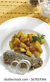Fried herring with fried potatoes, elevated view