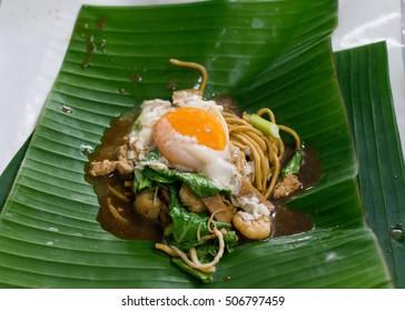 "Fried Hokkien Noodles or ""Hokkien Mee"" with egg on banana leaf Traditional food of Phuket, Thailand"