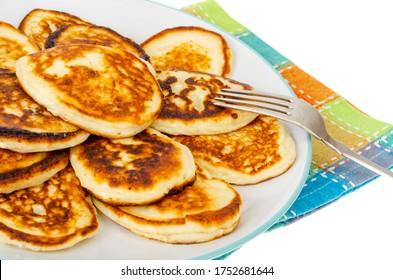 Frittierte hausgemachte Pfannkuchen auf Teller, bunte Serviette. Studioaufnahme