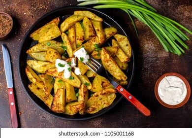 Fried hot potatoes in a pan, green onions, spices. White sauce. Potatoes cooked in a rustic style. Dark background, fork, knife.