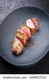 Fried Iberian pork fillet sliced with spice as closeup in a cast iron design plate