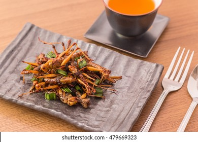 Fried insects - Grasshopper insect crispy with pandan after fried and add a light coating of sauce and garnish Thai pepper powder with fork and spoon, tea, on wooden background, Select focus