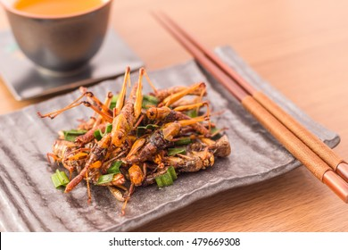 Fried insects - Wood worm insect crispy with pandan after fried and add a light coating of sauce and garnish Thai pepper powder with fork and spoon, tea, on wooden background, Select focus