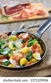 Fried Italian gnocchi with fresh spinach leaves, crispy roasted South Tyrolean bacon and parmesan cheese served in a frying pan