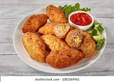 fried juicy breaded meat croquettes with melted cheese filling on a white plate with cucumber salad and tomato sauce, view from above, close-up