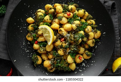 Fried kale and potato gnocci with chilie, peccorino cheese and lemon wedges in black plate. Italian food