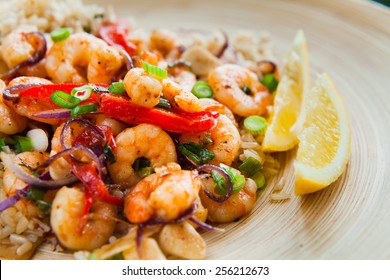 Fried king prawns with brown rice and vegetables: red pepper and onions. Served on a wooden plated with cut chives, spring onions and two pieces of lemon.Macro perspective, nobody, restaurant, menu.