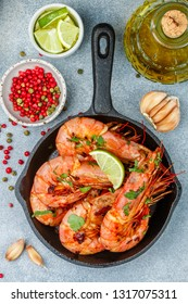Fried king prawns with garlic, pepper, lime and parsley (cilantro). Large shrimp. Langoustine.  Selective focus