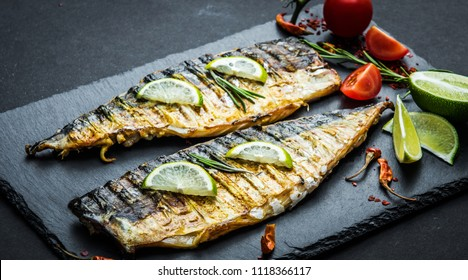 Fried mackerel fillets with lime on black slate board