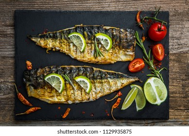 Fried mackerel fillets on wooden table, top view