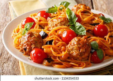 Fried meat balls and pasta spaghetti with eggplant, cheese in a tomato sauce close-up on a plate on a table. horizontal