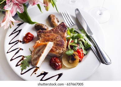 Fried meat on a bone with vegetables on a plate.Barbeque Steak Dinner