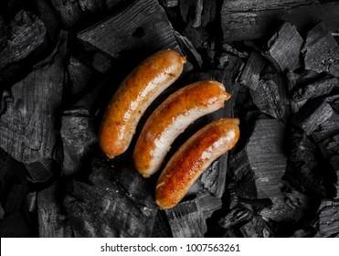 Bratfleischwürste auf schwarzem Hintergrund von Holzkohle. Gekochte saftige Jagdwürste auf Holzkohle. Bratwürste auf Holzkohle. Köstliche Bratwürste auf Kohlen, Nahaufnahme. Von oben anzeigen