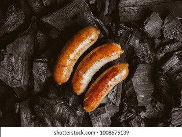 Fried meat sausages on a black background of charcoal. Cooked juicy hunting sausages on charcoal. Fried sausages on charcoal. Delicious fried sausages on coals, close-up photo.Vintage photo processing