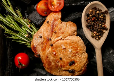 Fried meat steak on a black background of charcoal. Cooked juicy steak with tomato and rosemary on the coals. Veal / beef steak on charcoal. Grilled delicious marinated steak on coals, closeup photo.