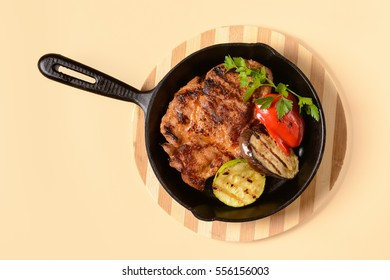 Fried meat with vegetables in a pan on light background
