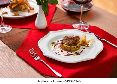 Fried meat and vegetables with wine and nice bouquet of flowers stands on the table in a restaurant. Romantic evening time.