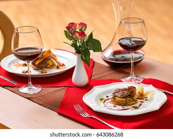 Fried meat and vegetables with wine and nice bouquet of flowers stands on the table in a restaurant.