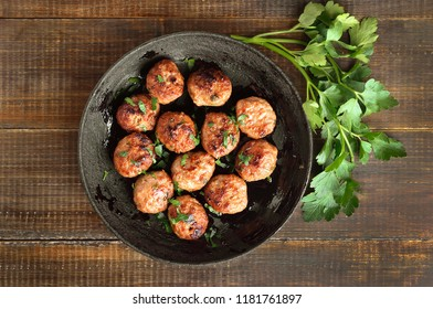 Fried meatballs and fresh parsley on wooden table, top view