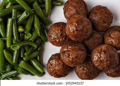 fried meatballs and green beans on white plate. top view