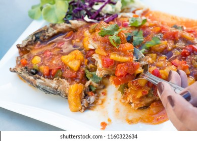Fried milkfish (Bangus) to eat Topped with mango sauce, carrots, onions, lime juice, lime fish sauce,Thailand style.