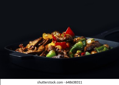 Fried mix of meat and vegetables in cast iron pan
