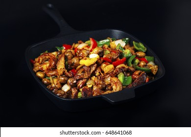 Fried mix of meat and vegetables in cast iron pan on dark background