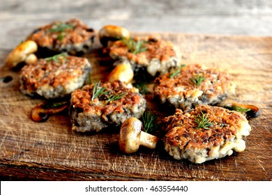 Fried mushroom cutlets decorated with dill on a wooden background. Agaricus recipe. Vegetarian and diet food