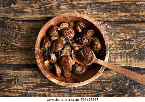 Fried mushrooms with onion in bowl on wooden background, top view