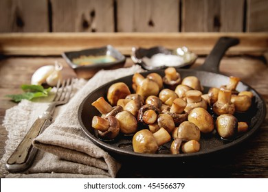 fried mushrooms with salt and pepper on a wooden background