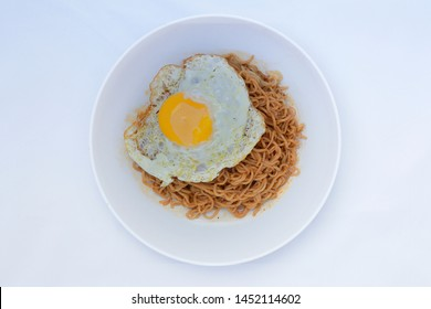 Fried noodle (Indomie Goreng) with sunny side up egg, served on white plate. Top view close up detail