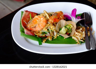 Fried noodle of Padthai with shrimps on top, a Thai famous food in a white plate on black dinning table