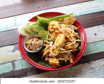 Fried noodle Thai style (Pad thai), Wooden table background.