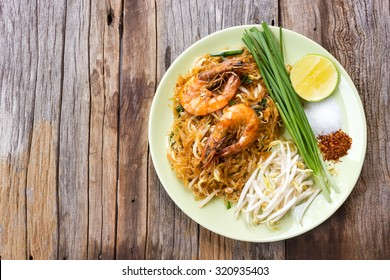 Fried noodle Thai style with prawns. On wood table. Top view.