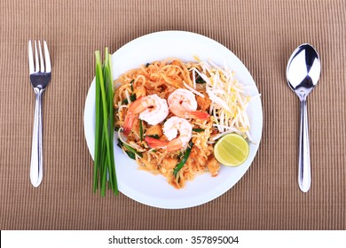 Fried noodle Thai style with prawns, Stir fry noodles with shrimp in padthai style on table. Top view isolate white