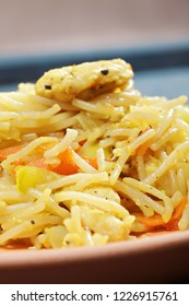 Fried noodles in plate over wooden board. Vertical closeup shot