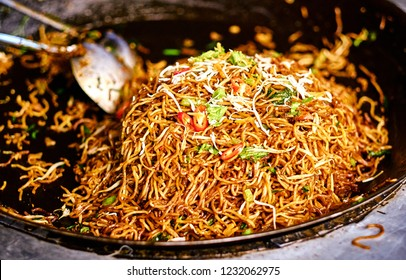 Fried noodles in a wok. Asian, Indian and Chinese street food. Food court on local market of Langkawi island, Malaysia.Traditional asian street food.