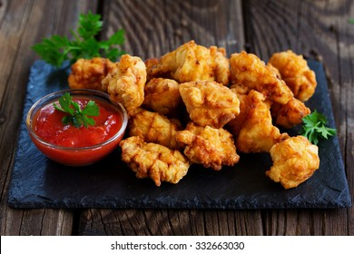 Fried nuggets of chicken breast with sauce.