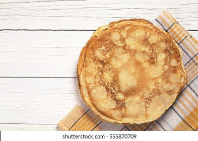 Fried pancakes on white wooden table, top view. Space for text