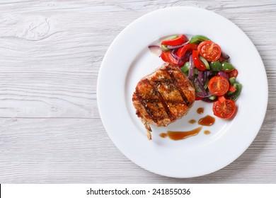 Morceau de porc frit avec salade de légumes sur une assiette vue en gros plan d'en haut. horizontal