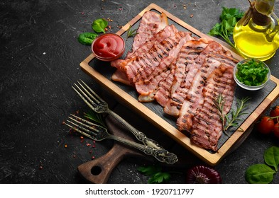 Fried pieces of bacon on a black stone board. Top view. Free space for text.