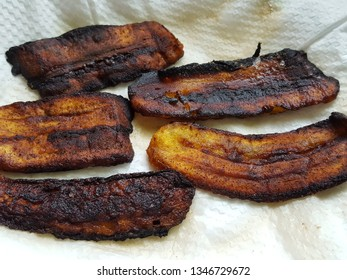 Fried plantains draining on paper towels after being fried. The shot captures the sweetness of the plaints and guides as to how to drain the excess oil out of the plain-tins.