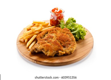 Fried pork chop with french fries on cutting board