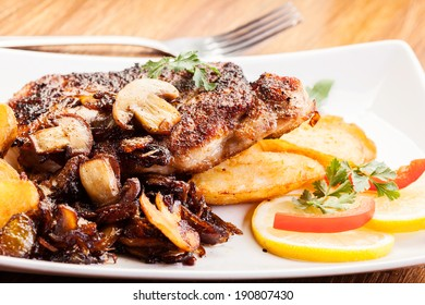 Fried pork chop with mushrooms and chips  on a plate