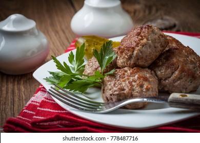 Fried pork meatballs on a white plate.